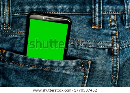Photo of  Smartphone with a green screen in the back pocket of jeans pants. Phone with chroma key close-up.
