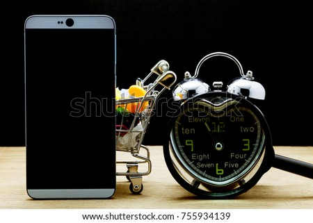 Smartphone with alarm clock and shopping cart on wooden floor,time to online shopping concept  #755934139