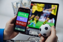 Smartphone with betting mobile application and male's hand with soccer ball. Sport and betting concept