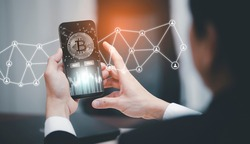 Smartphone with Bitcoin chart on-screen among piles of Bitcoin concept. businessman touch on mobile app screen with big BUY and SELL buttons on the stock market, Cryptocurrency and finance.