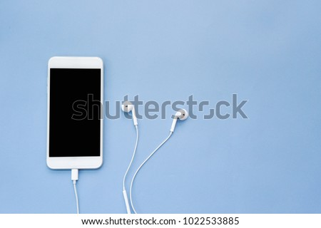 Smartphone with Blank Screen and Earphones on Blue Background Top View