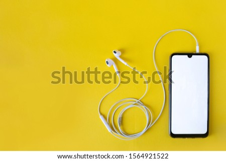 Smartphone with blank white screen connects to earphones on yellow background - top view. Earphone connected to cellphone.