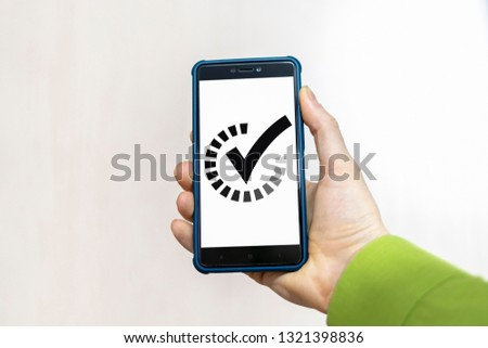 Smartphone with check mark and progression bar in a hand. In progress completed mobile app concept. #1321398836