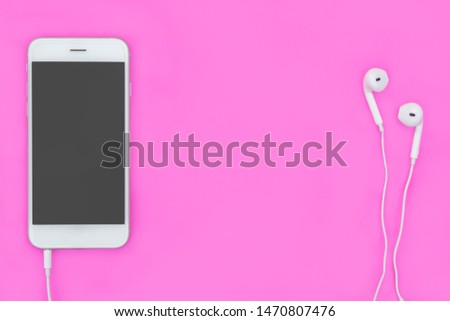 Smartphone with Earphones on pink background with copy space and clipping path. Flat lay. Top view.
