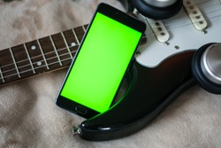 Smartphone with green screen on an Electric Guitars