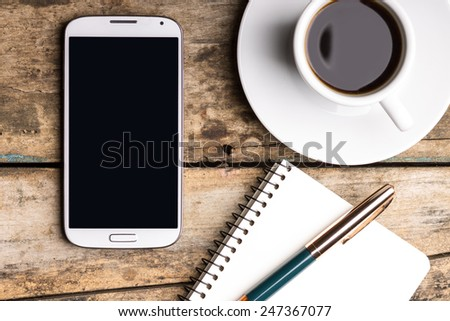 Smartphone with notebook and cup of strong coffee on wooden background. Cell phone with writing set with espresso #247367077
