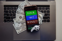 Smartphone with online betting application, dollar bills and soccer ball on a laptop. Gambling concept
