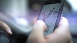 Smartphone with stock market graph on a touch screen device close up, focused shot. Hands with a mobile phone, checking stock market data, blurred bokeh