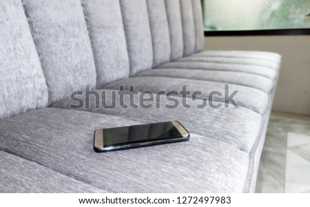 Smartphones forgotten on the sofa,Mobile phone put forgotten ,Smartphone with an on the sofa of a restaurant,Concept of mobile communication in travel and lost gadgets,Copy space