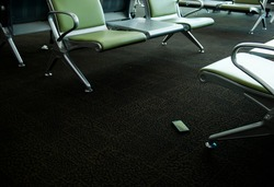 Smartphones found on carpet under the seat of a international airport, Mobile phone dropped on the ground and forgotten, Concept of mobile communication in travel and lost gadgets in the airport,