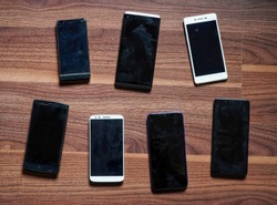 Smartphones, old and used smartphones on wood texture background