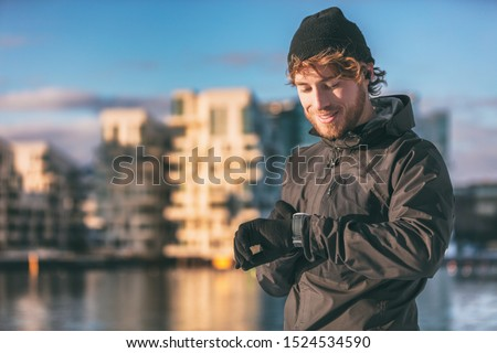 Smartwatch runner athlete man looking at his wearable technology smart watch on morning outdoor run checking his heart rate data running workout jogging through city streets.