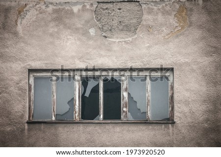 Smashed glass on a broken window on an abandoned and decaying factory industrial building left neglected. ストックフォト ©