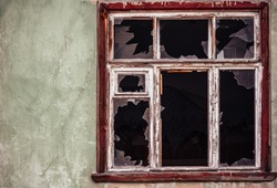 Smashed glass Window with old wooden frame on grunge wall damaged house