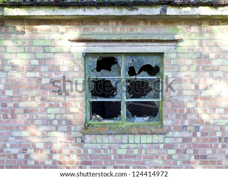 Smashed panes of glass in a window in a dilapidated old house