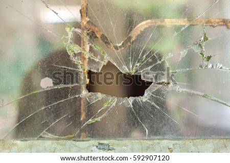 Smashed window pane with a hole in the middle #592907120