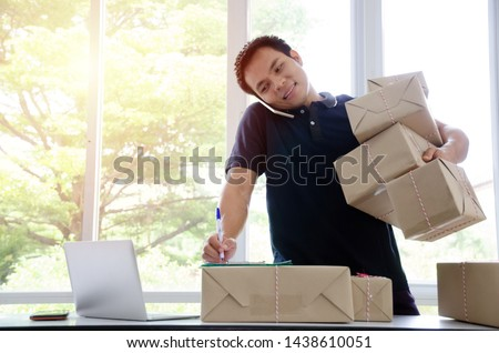 SME. handsome young asian delivery man happy after new order from customer and lifting many packaging parcel box with mobile phone in home office, small business owner, cargo, mail, shipping concept