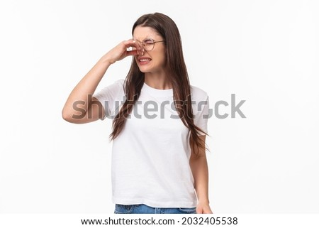 Smells disgusting. Portrait of disgusted and displeased young beautiful girl in glasses, shut nose with fingers and look away with grimace as something have awful smell, reek, stand white background Stok fotoğraf ©