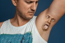 Smelly armpits in men. Concept of twisted panting face from bad smell