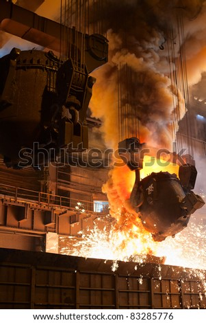 Smelting orange metal in a metallurgical plant. Liquid iron from the ladle