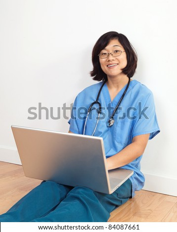 Smiing female nurse or doctor, seated on floor with laptop computer
