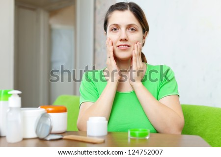 Smiing young woman in doing cosmetic mask on her face at home interior - stock photo