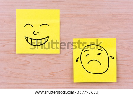 Smile and cry faces on two pieces of memo paper #339797630