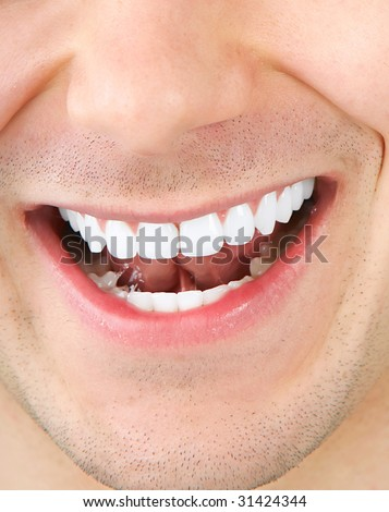 Smile and teeth of a young smiling  man. Close up