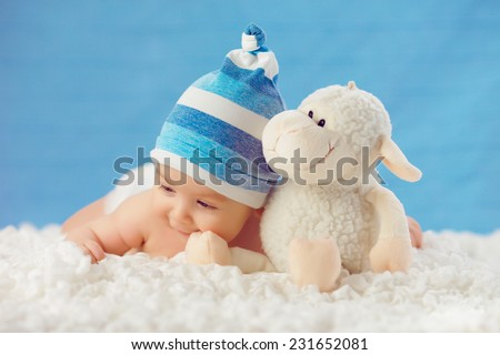 Smile baby in hat, hugging toy on a white bedspread, on a blue background