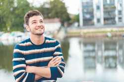 Smile beautiful cheerful man in front of river thinking positiv, outdoors