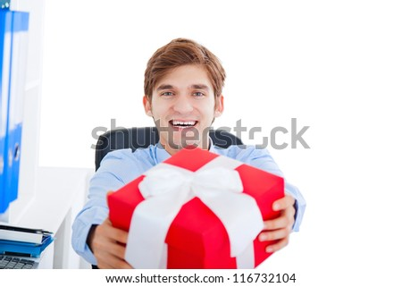 smile business man give red present gift box with bow sitting in office, happy young businessman isolated over white background