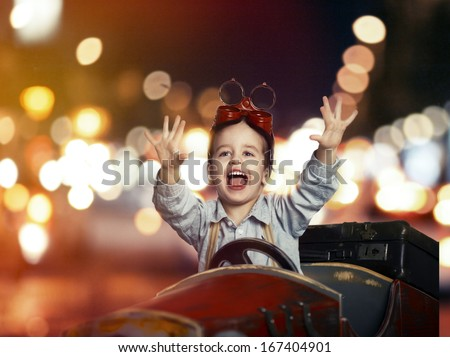 Smile child in wooden car in night on street