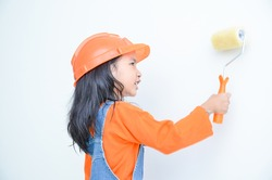 Smile cute asian little girl holding paint roller with copy space in the white room