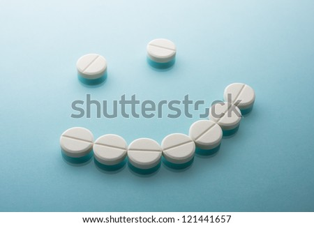 Smile face  from pills  on blue background