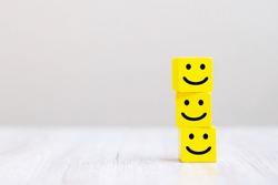 Smile face symbol on yellow wooden cube blocks. Service rating, ranking, customer review, satisfaction and feedback concept.