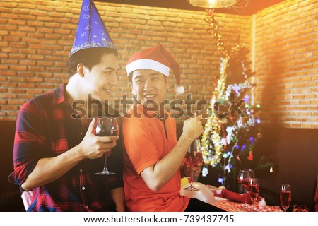 Smile Gay men couple with santa hats looking each other and celebrating Christmas party. Xmas celebration with wine or champagne drink, balloons, X'mas tree. One guy wanna go outside to private room. #739437745