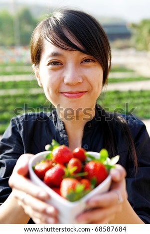 smile girl give you bowl of strawberries