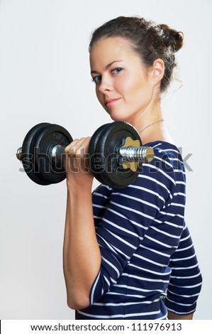 smile girl with dumbbell in action on gray background