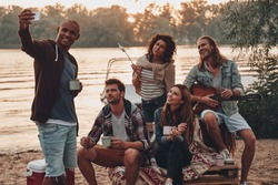 Smile! Group of young people in casual wear smiling and taking selfie while enjoying beach party near the lake