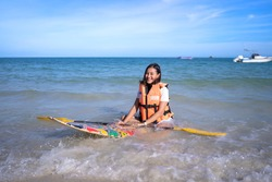 smile happy Asian woman with life-saving jacket sit on small paddleboard holding oar at wavy sea beach, girl relax on vacation in summer
