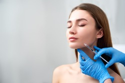 Smile lifting and lip augmentation. Beautician doctor hands doing beauty procedure to female face with syringe. Young woman's mouth countouring with filler injection. Marionette lines treatment.