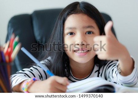 Smile little Asian girl showing thumb up and doing homework with happiness for self learning and education concept select focus shallow depth of field