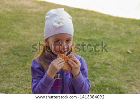 Smile little girl. A girl stands on the sidewalk. The girl eats a pie. Childhood childhood.