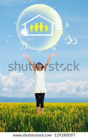 Smile little girl showing on family symbol in big soap bubble on yellow flower field