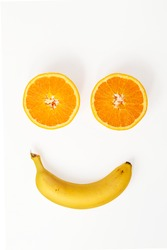 Smile made by two halves of an orange and banana on a white background
