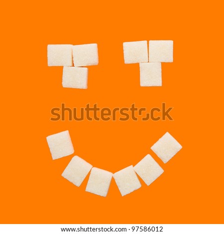 Smile symbol, composed of cubes of sugar. Isolated on orange background with clipping path