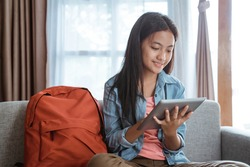 smile young teen using tablet pc while staying home