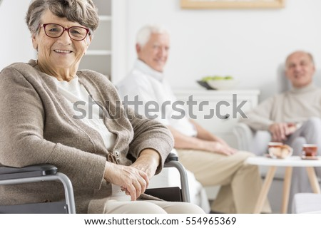 Smiled woman on a wheelchair at nursing home
