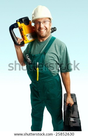 Smiled workman in helmet, glasses and overalls hold perforator on the shoulder and big black suitcase in hand over white background