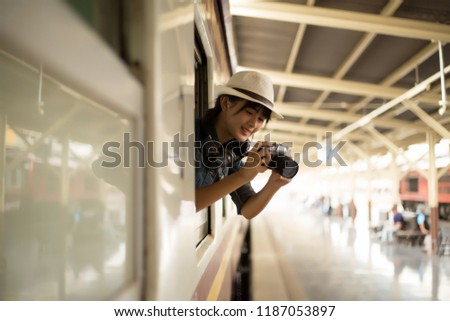 Smiles happily of young woman travels by train. takes pictures of nature on the out train window on the Train. copy space,,travel, backpack concept